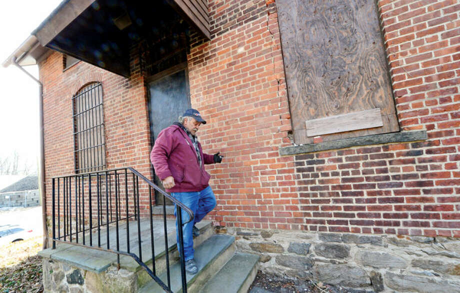 Hour photo / Erik Trautmann Tony Mauro works on the restoration of the old jailhouse on Smith St. The Norwalk Historical Society and the Norwalk Historical Commission are begining restoration of fire-damaged Smith Street Jailhouse and nearby historic barn.