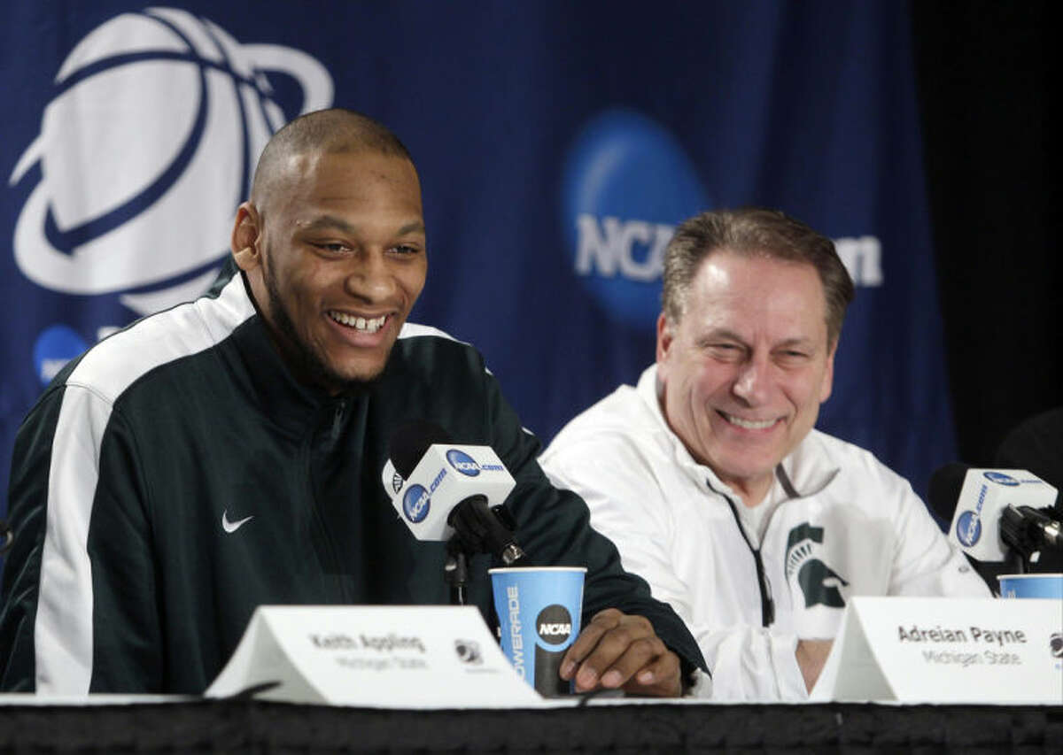 Michigan State's Adreian Payne, left, and head coach Tom Izzo react as Payene responds to a question during a news conference at the NCAA college basketball tournament Saturday, March 29, 2014, in New York. Michigan State plays Connecticut in a regional final on Sunday. (AP Photo/Frank Franklin II)