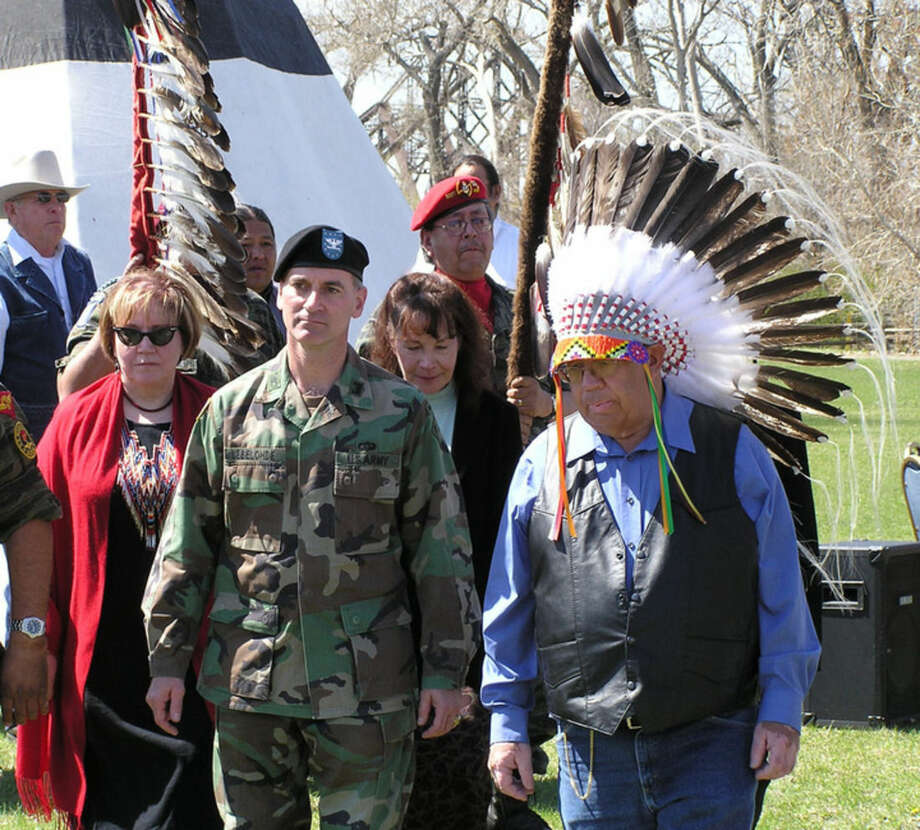 FILE - In this Tuesday, April 13, 2004 file photo, Mike Jandreau, right, attends a ceremony in Pierre, S.D. where he was honored with an eagle feather bonnet for his 25 years of service as chairman of the Lower Brule Sioux Tribe. An attorney for the tribe says Jandreau died at a Sioux Falls hospital on Friday, April, 3, 2015. (AP Photo/Joe Kafka)
