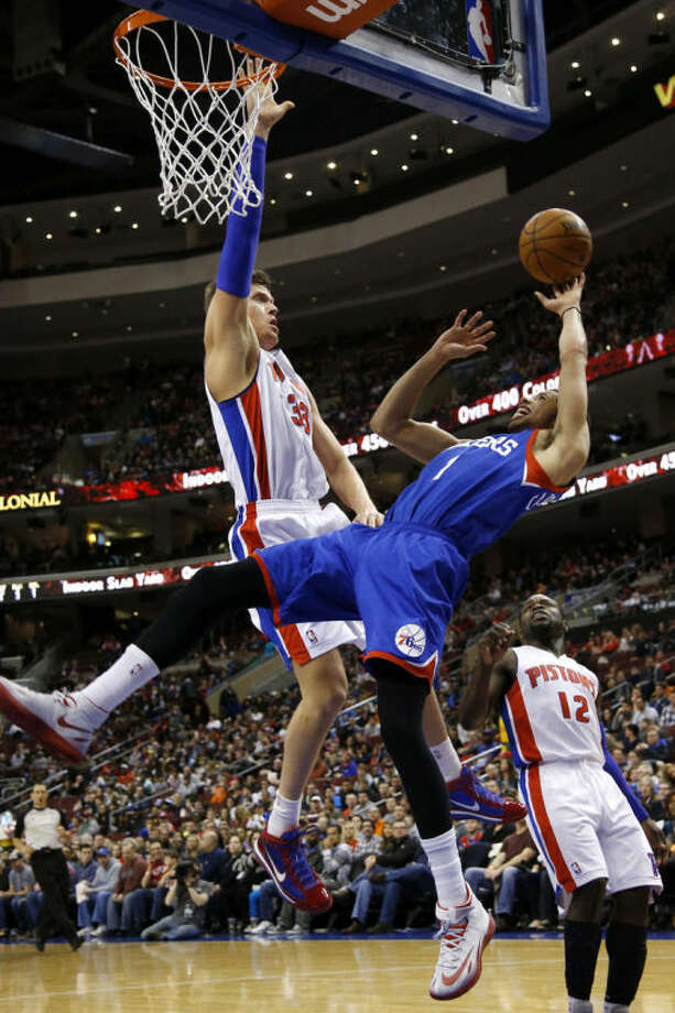 Philadelphia 76ers' Michael Carter-Williams (1) goes up to shoot against Detroit Pistons' Jonas Jerebko (33), of Sweden, and Will Bynum (12) during the first half of an NBA basketball game on Saturday, March 29, 2014, in Philadelphia. (AP Photo/Matt Slocum)