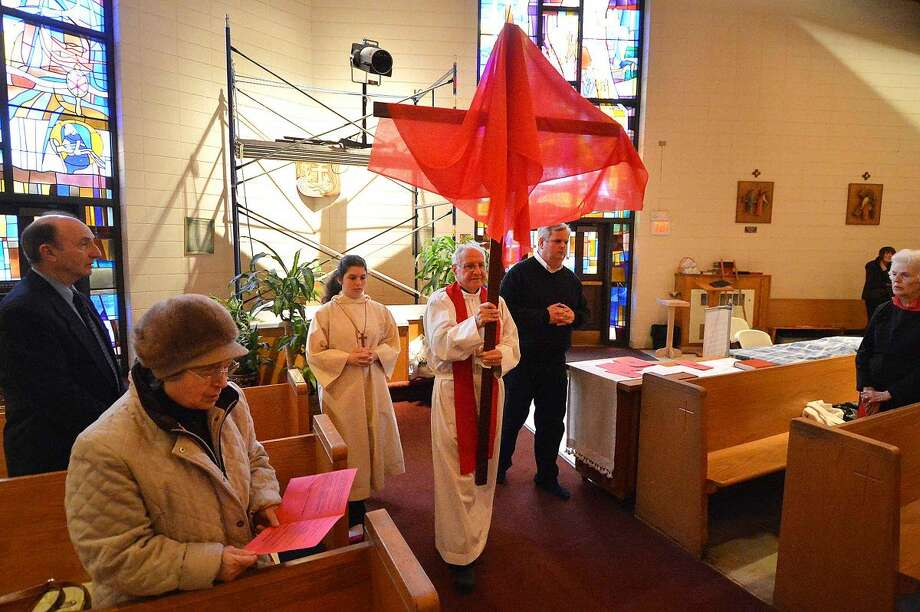 Hour Photo/Alex von Kleydorff Parochial Vicar Rev Joeseph Palacino walks the cross down the center aisle during Good Friday services incuding the Veneration of the Cross and the reading of The Passion at St Jerome Roman Catholic Church on Friday