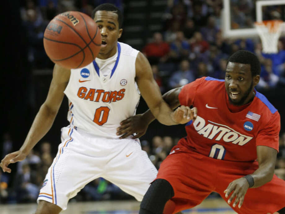 Florida guard Kasey Hill (0) and Dayton guard Khari Price (0) watch a loose ball during the first half in a regional final game at the NCAA college basketball tournament, Saturday, March 29, 2014, in Memphis, Tenn. (AP Photo/John Bazemore)
