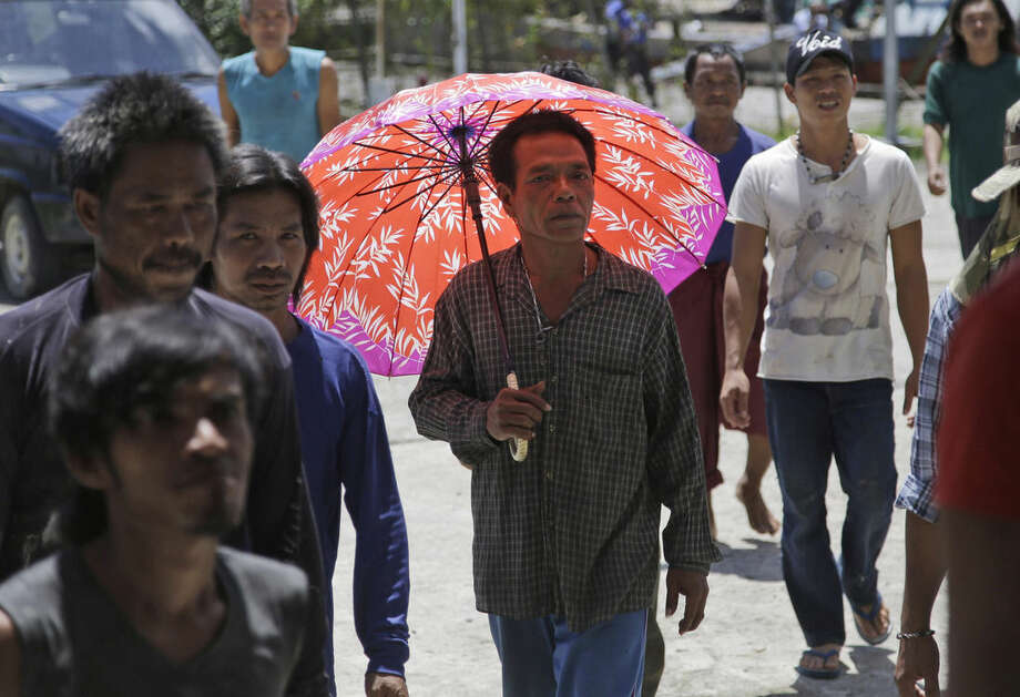 Foreign fishermen walk prior to being questioned by Indonesian officials at the compound of Pusaka Benjina Resources fishing company in Benjina, Aru Islands, Indonesia, Friday, April 3, 2015. Officials from three countries are traveling to remote islands in eastern Indonesia to investigate how thousands of foreign fishermen were abused and forced into catching seafood that could end up in the United States, Europe and elsewhere. (AP Photo/Dita Alangkara)