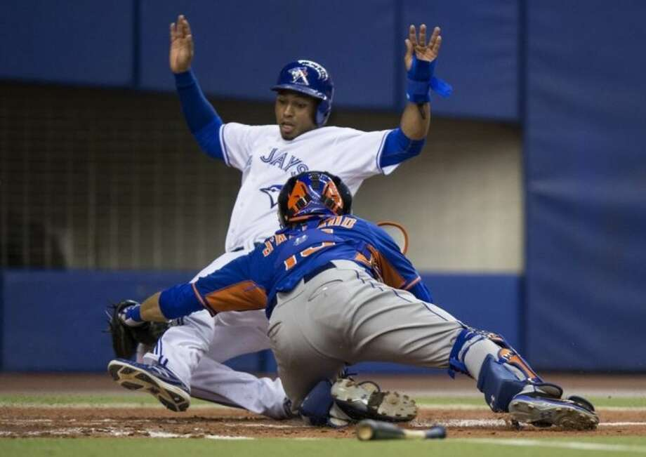 Toronto Blue Jays' Moises Sierra is tagged out at home plate by New York Mets' Travis d'Arnaud to end the third inning of an exhibition baseball game Saturday, March 29, 2014, in Montreal. Sierra tried to score from first base on a hit a by Melky Cabrera. (AP Photo/The Canadian Press, Paul Chiasson