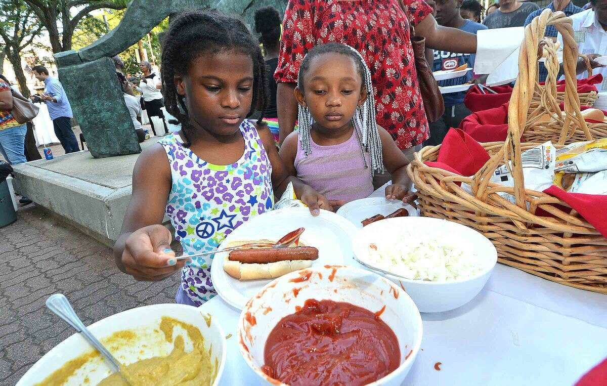 Hour Photo/Alex von Kleydorff Amira Stackhouse and Aryanna Brown get some ketchup on their hot dogs during Community Summer Mixer sponsored by GGP. The party was to let people know about the proposed mall for South Norwalk. Residents were treated to free hot dogs hamburgers and all the trimmings and were entertained by a DJ, face painting and a balloon artist in the plaza at 50 Washington st.