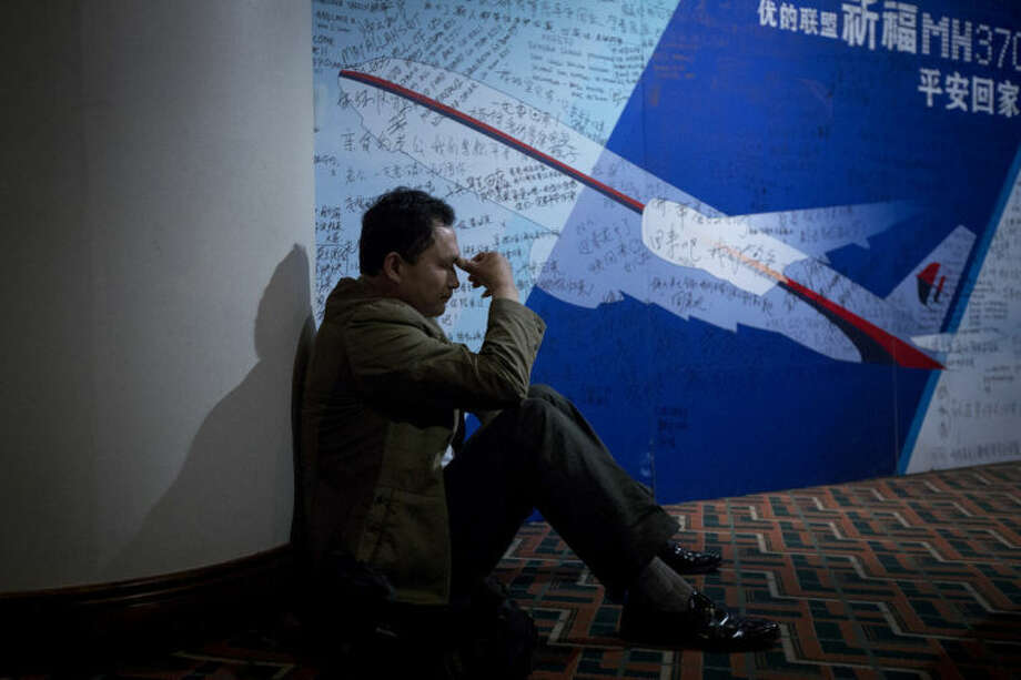 AP photo / Alexander F. YuanA man, one of the relatives of Chinese passengers onboard Malaysia Airlines Flight 370, rests near a board covered with written wishes at a hotel in Beijing, China Saturday.
