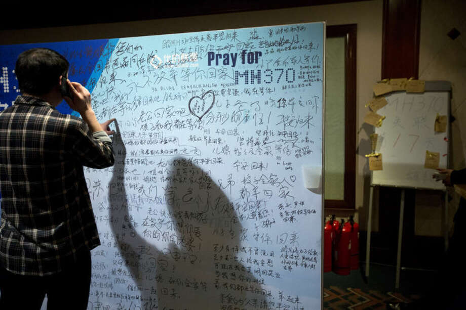 """A man, one of the relatives of Chinese passengers onboard Malaysia Airlines Flight 370, talks on his mobile phone as he touches a board covered with written wishes, while a board, right, marks the 17th day since the flight lost contact, at a hotel in Beijing, China, Saturday, March 29, 2014. Some of the wishes are """"Dear husband, you must stay strong, I am waiting for you. Dear father, please be back home safely and the whole family is here waiting for you."""" (AP Photo/Alexander F. Yuan)"""
