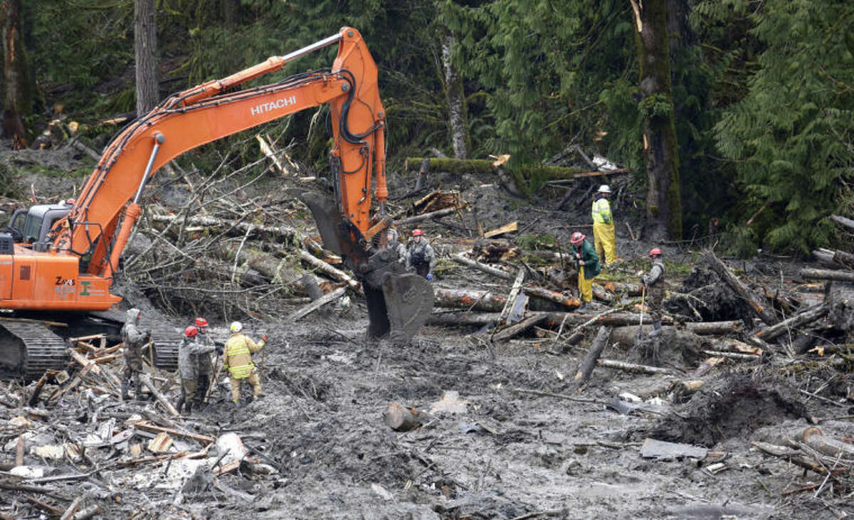 Searchers work at the scene of a deadly mudslide Saturday, March 29, 2014, in Oso, Wash. Besides the more than two dozen bodies already found, many more people could be buried in the debris pile left from the mudslide one week ago. Ninety people are listed as missing. (AP Photo/Elaine Thompson, Pool)