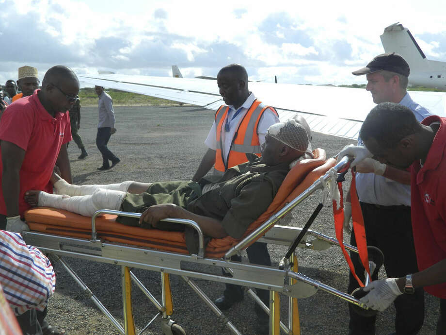 A victim of Thursday's university attack is assisted to a plane by medical staff prior to being airlifted to Nairobi, at the Garissa military airstrip, Garissa, Kenya, Friday, April 3, 2015. Al-Shabab gunmen rampaged through a university in northeastern Kenya at dawn Thursday, killing scores of people in the group's deadliest attack in the East African country. Four militants were slain by security forces to end the siege just after dusk. (AP Photo)