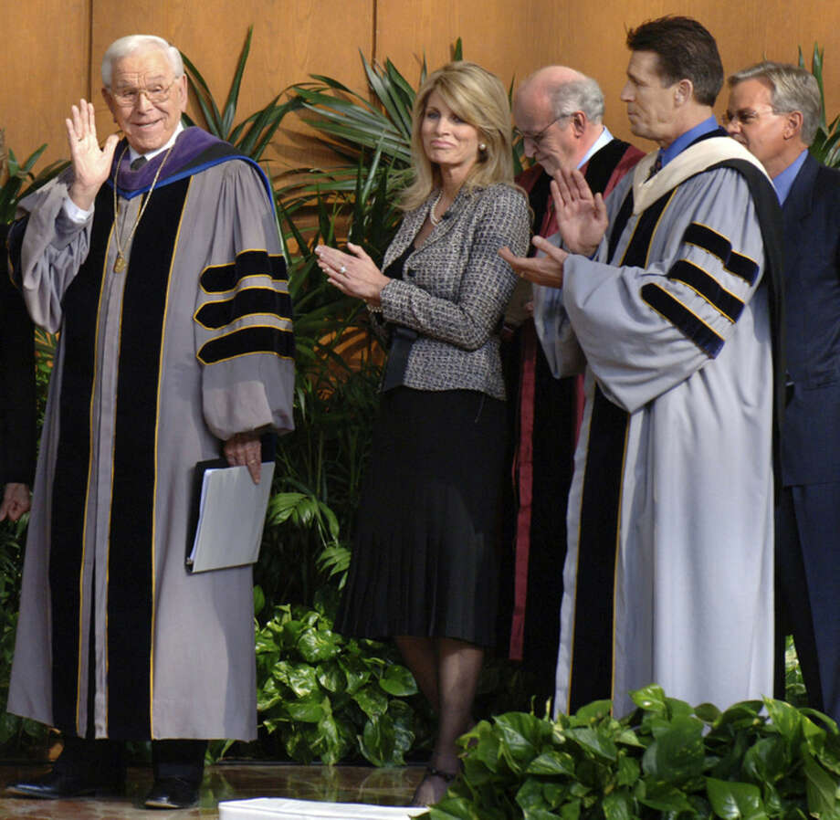 "FILE - In this Jan. 22, 2006, file photo, Rev. Robert H. Schuller, left, greets church members and visitors during the celebration service for the installation of his son Dr. Robert A. Schuller as senior pastor at Crystal Cathedral in Garden Grove, Calif. Robert H. Schuller, the Southern California televangelist who brought his message of ""possibility thinking"" to millions, died early Thursday, April 2, 2015, in California. He was 88. (AP Photo/Orange County Register, Sang H. Park, File)"
