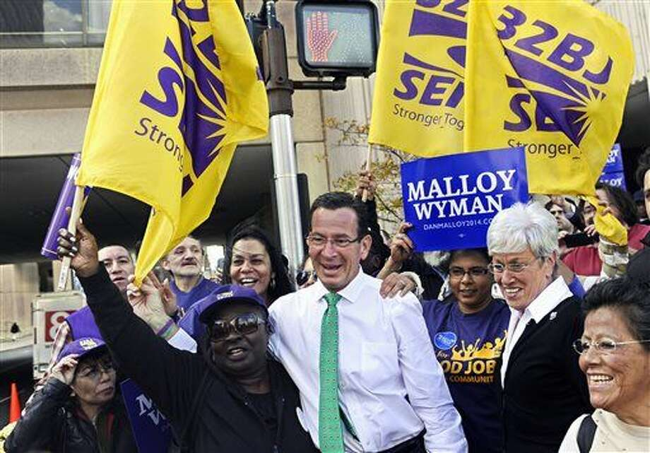 Members of 32BJ SEIU, property service workers union, stand with Gov. Dannel P. Malloy, center, before a debate between Malloy and Republican candidate Tom Foley, Thursday, Oct. 9, 2014, in Hartford, Conn. Organized labor is devoting millions of dollars and countless man-hours to re-elect Gov. Dannel P. Malloy, a Democrat considered an important ally of unions despite a 2011 clash with unionized state employees in which he threatened massive layoffs during a budget impasse.