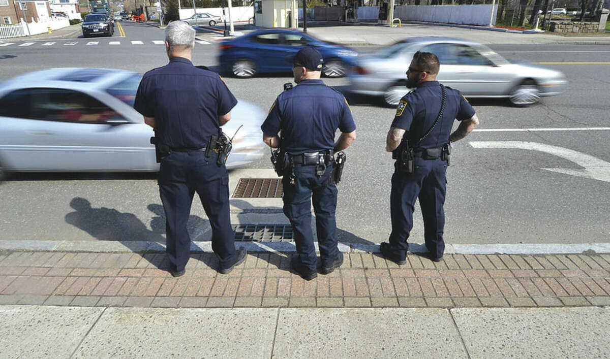 Hour Photo/Alex von Kleydorff In this file photo, Norwalk Police Officers Jamie Wright, J. Zavitz and David Geismar wait on the side of West Avenue for radio calls from a block north where another officer is looking for drivers on cell phones, during distracted driving enforcement on Tuesday.