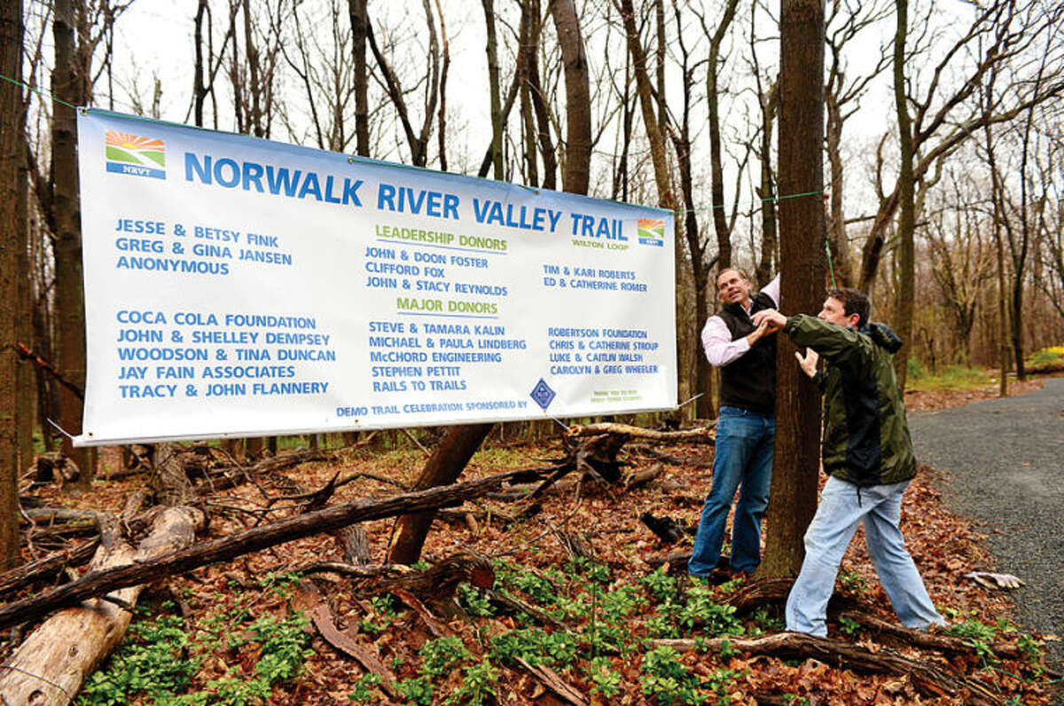 Hour photo / Erik Trautmann dab Berg and Jason Dahl put up a banner thanking those responsible for The Norwalk River Valley Trail's Wilton Loop during the grand opening Saturday