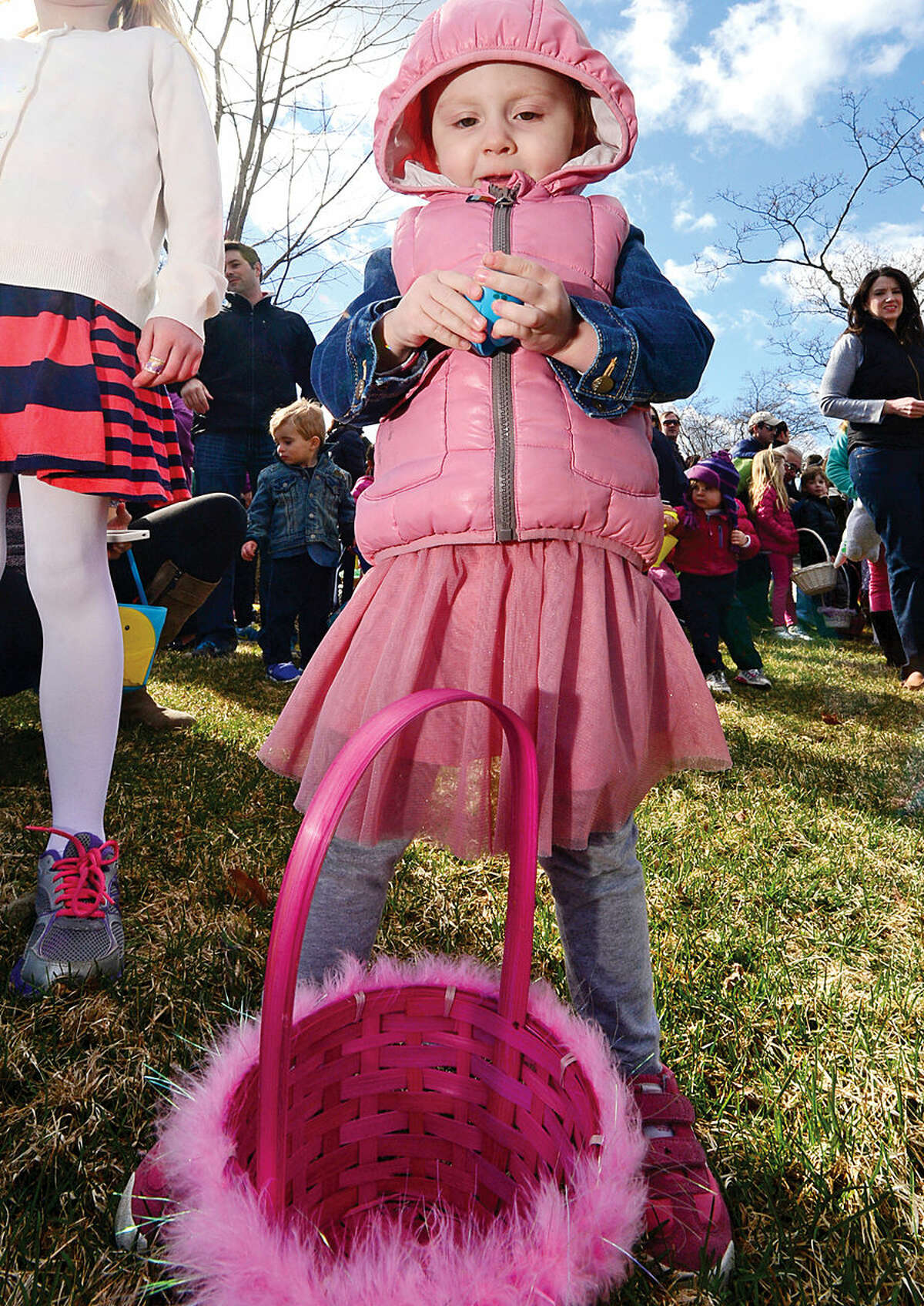 Hour photo / Erik Trautmann Lily Ricciardi, 2, looks at an egg during The Rowayton Community Association's annual Easter Egg Hunt Saturday at the Rowayton Community Center.
