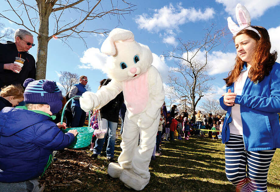 Hour photo / Erik Trautmann Farrell Aldrich helps the Easter Bunny distribute candy during The Rowayton Community Association's annual Easter Egg Hunt Saturday at the Rowayton Community Center.
