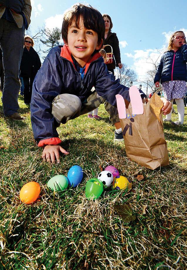 Hour photo / Erik Trautmann Altan Cakir, 6, looks for eggs during The Rowayton Community Association's annual Easter Egg Hunt Saturday at the Rowayton Community Center.