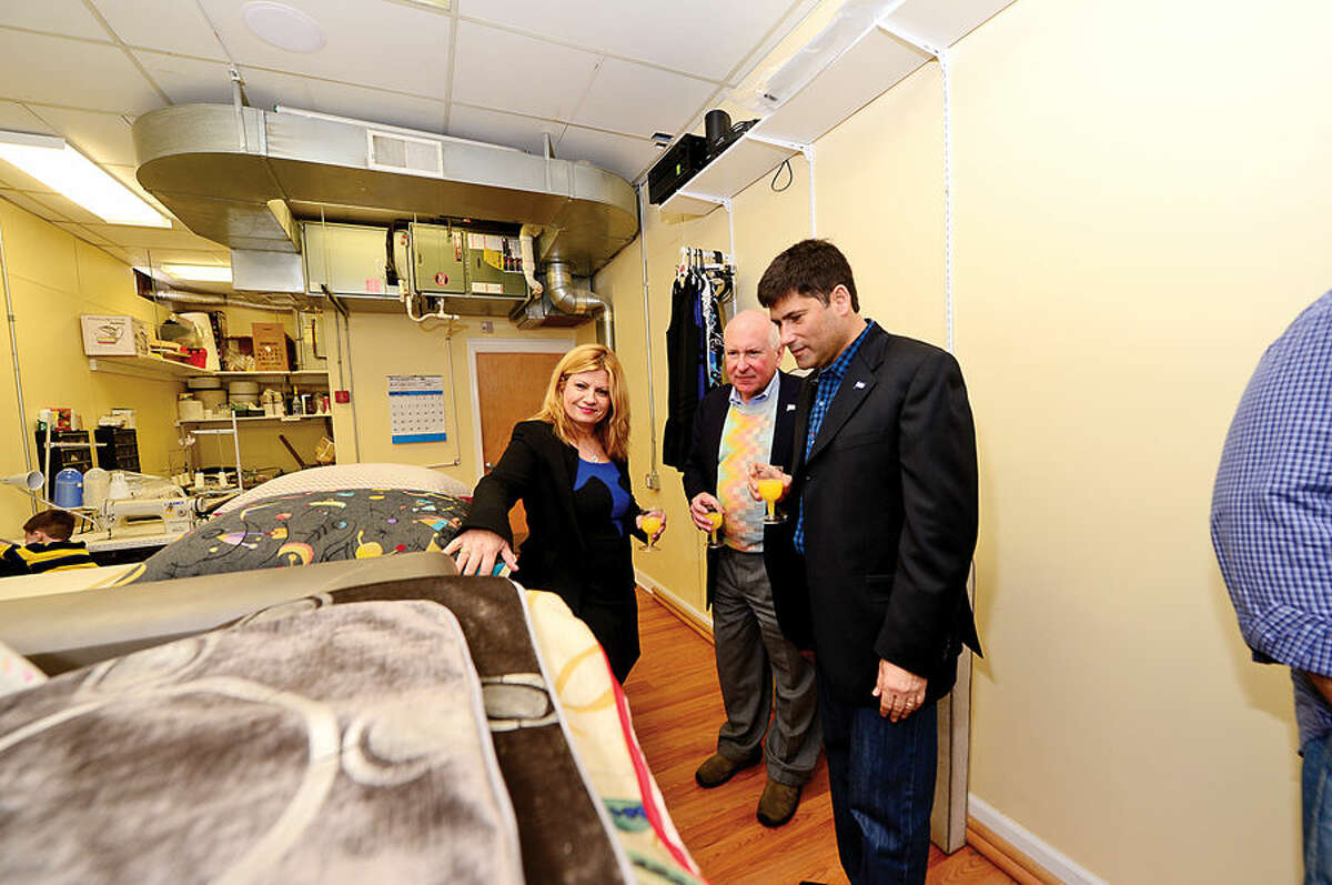 Hour photo / Erik Trautmann Saugatuck Fabric co -owner Leonora Silber chats with Wesport First Selectman Jim Marpe and Second Selectmen Avi Kaner during the grand opening of Saugatuck Fabrics in Westport Saturday.