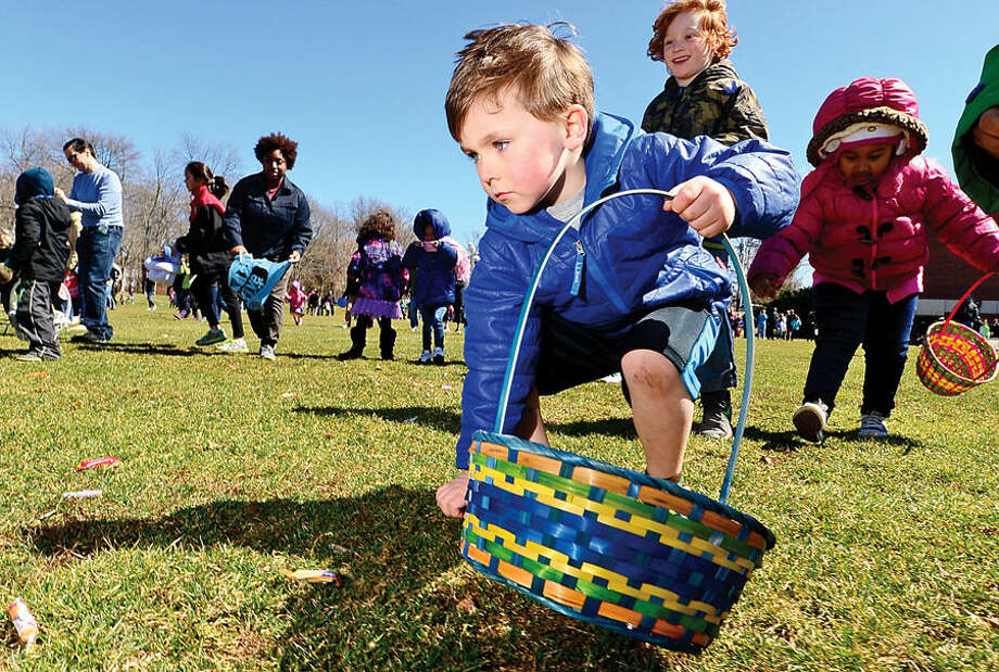 Hour photo / Erik Trautmann Colin Robinson, 5, and nearly two hundred children take part in the 64th annual Greens Farms Volunteer Fire Company Easter Egg Hunt at Long Lots School School Saturday