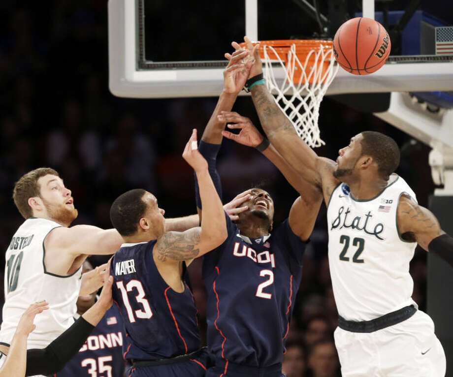 Michigan State's Matt Costello, left, and teammate Branden Dawson, right, battle under the basket with Connecticut's Shabazz Napier (13) and DeAndre Daniels in the first half of a regional final at the NCAA college basketball tournament on Sunday, March 30, 2014, in New York. (AP Photo/Seth Wenig)