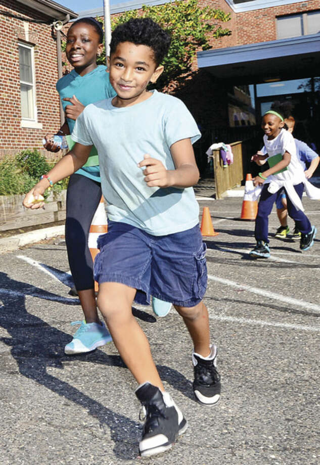 """Hour photo / Erik Trautmann Side by Side School student Carlin Aponte participates in the Save the Children's """"Run for Kids"""" Friday morning at the school. """"Run for Kids"""" is an annual Save the Children fundraising event to help kids in approximately 40 countries with roughly 20,000 participants. Kids come together in teams to challenge themselves and raise funds that will help change the lives and futures of children around the world."""