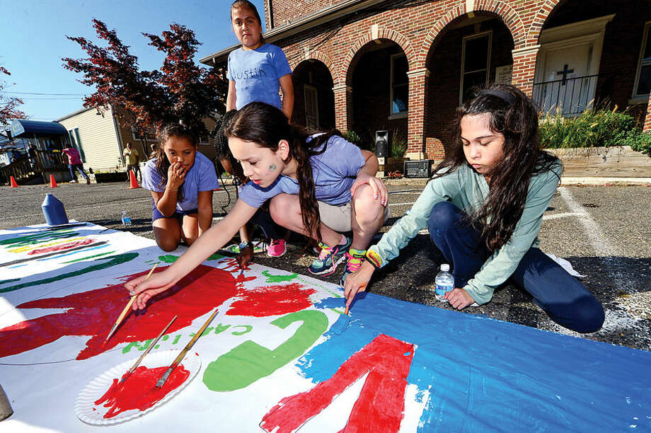 "Hour photo / Erik Trautmann Side by Side School students Brisyda Sandoval and Cainab Khan paint a banner for Save the Children's ""Run for Kids"" Friday morning at the school. ""Run for Kids"" is an annual Save the Children fundraising event to help kids in approximately 40 countries with roughly 20,000 participants. Kids come together in teams to challenge themselves and raise funds that will help change the lives and futures of children around the world."