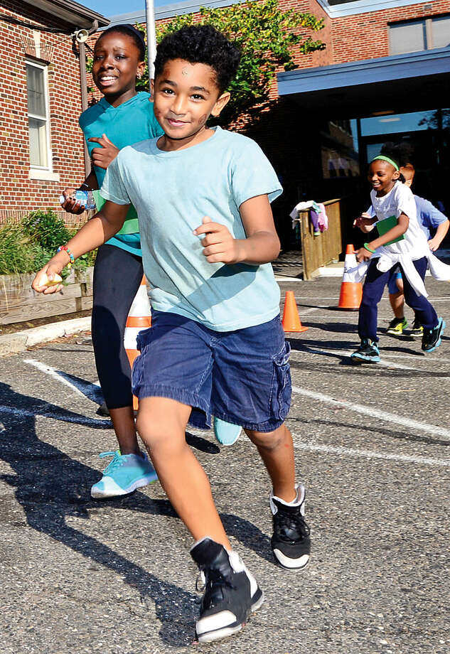 "Hour photo / Erik Trautmann Side by Side School student Carlin Aponte participates in the Save the Children's ""Run for Kids"" Friday morning at the school. ""Run for Kids"" is an annual Save the Children fundraising event to help kids in approximately 40 countries with roughly 20,000 participants. Kids come together in teams to challenge themselves and raise funds that will help change the lives and futures of children around the world."