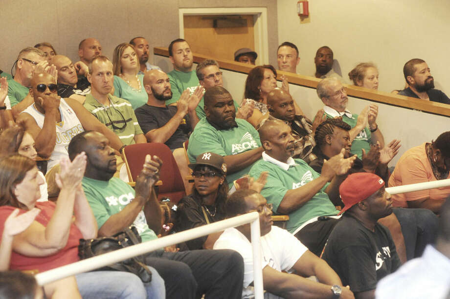 Hour photo/Matthew VinciCustodians and union members of Local 1042 sit side by side with supporters of Shirley Mosby Tuesday night at Norwalk City Hall. Discussions focused on a plan to outsource custodian services at two schools in Norwalk, and on a petition to have two Norwalk Board of Education members resign over alleged racism issues.