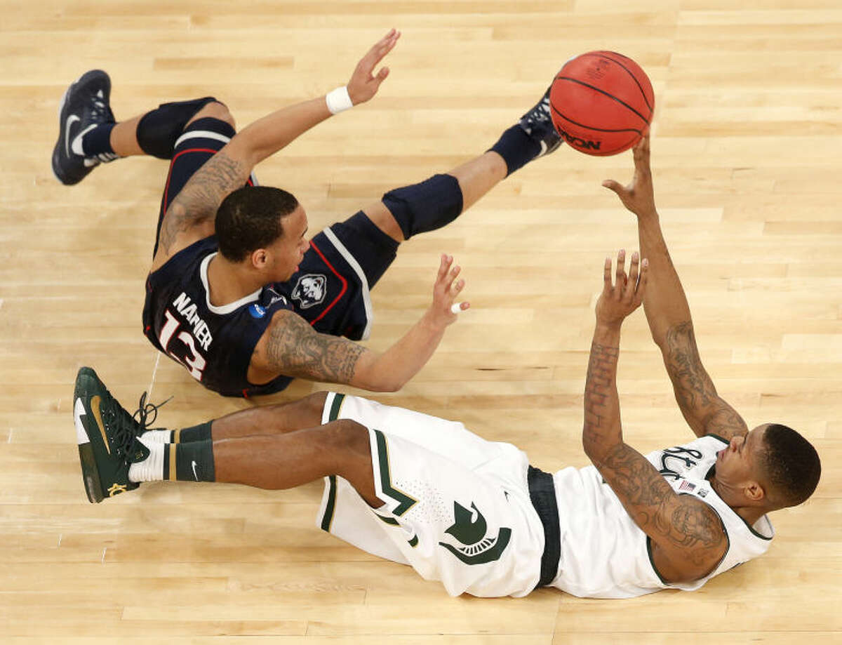Connecticut guard Shabazz Napier, left, and Michigan State guard Keith Appling fall while competing for a loose ball during the first half in a regional semifinal at the NCAA college basketball tournament on Sunday, March 30, 2014, in New York. (AP Photo/Julio Cortez)