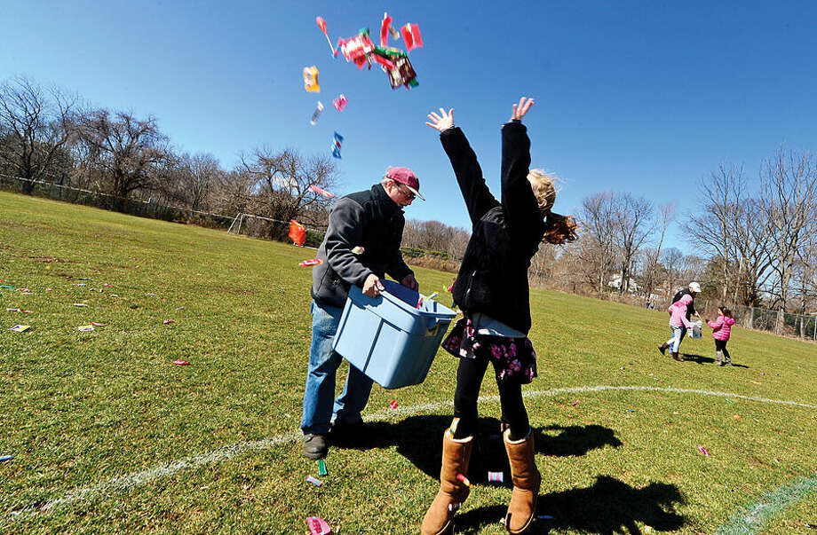 Hour photo / Erik Trautmann Dave palmer and Isabella Shafer spread candy for nearly two hundred children during the 64th annual Greens Farms Volunteer Fire Company Easter Egg Hunt at Long Lots School School Saturday