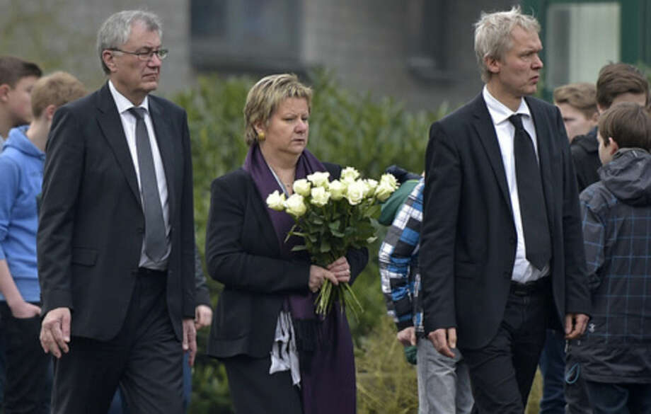 Education Minister of the German state North Rhine-Westphalia Sylvia Loehrmann, center, arrives with flowers in front of the Joseph-Koenig Gymnasium in Haltern, western Germany, Wednesday, March 25, 2015, one day after 16 school children and two teachers were among the 150 victims that died in the Germanwings plane crash in the French alps on the way from Barcelona to Duesseldorf. (AP Photo/Martin Meissner)