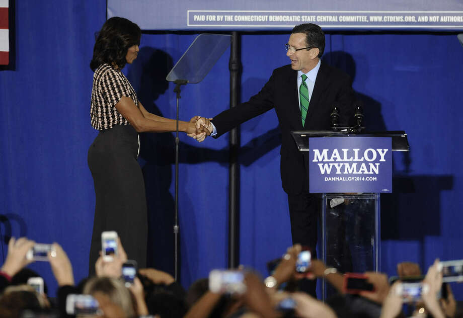 First lady Michelle Obama shakes hanks with Connecticut Gov. Dannel P. Malloy during a rally for Malloy, Thursday, Oct. 30, 2014, in New Haven, Conn. (AP Photo/Jessica Hill)