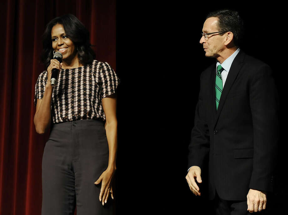 First Lady Michelle Obama, left, speaks as Connecticut Gov. Dannel P. Malloy listens after surprising a group of supporters in an overflow room to a rally, Thursday, Oct. 30, 2014, in New Haven, Conn. (AP Photo/Jessica Hill, Pool)