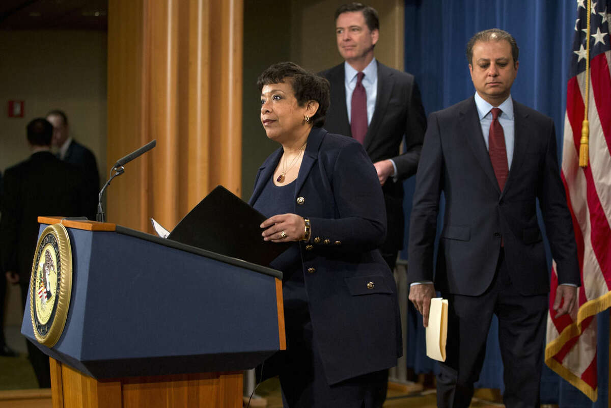 Attorney General Loretta Lynch, accompanied U.S. Attorney Preet Bharara of the Southern District of New York, right, and FBI Director James Comey, arrives to a news conference at the Justice Department in Washington, Thursday, March 24, 2016. Seven hackers tied to the Iranian government were charged Thursday in a series of punishing cyberattacks on a small dam outside New York City and on dozens of banks _ intrusions that reached into American infrastructure and disrupted the financial system, U.S. law enforcement officials said. (AP Photo/Jacquelyn Martin)