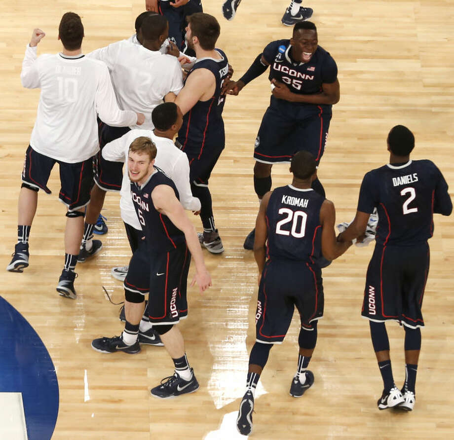 Connecticut players celebrate after beating Michigan State during a final at the NCAA college basketball tournament, Sunday, March 30, 2014, in New York. (AP Photo/Julio Cortez)