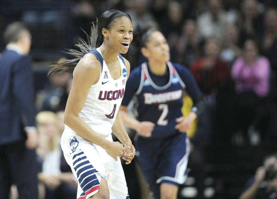 Connecticut's Moriah Jefferson celebrates a made basket in front of Duquesne's Deva'Nyar Workman during the first half of a second round women's college basketball game in the NCAA Tournament, Monday, March 21, 2016, in Storrs, Conn. (AP Photo/Jessica Hill)