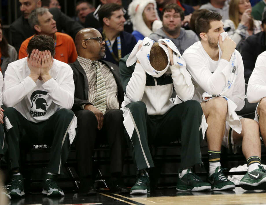 Michigan State players watch the final moments of their 60-54 loss to Connecticut in a regional final at the NCAA college basketball tournament, Sunday, March 30, 2014, in New York. (AP Photo/Seth Wenig)