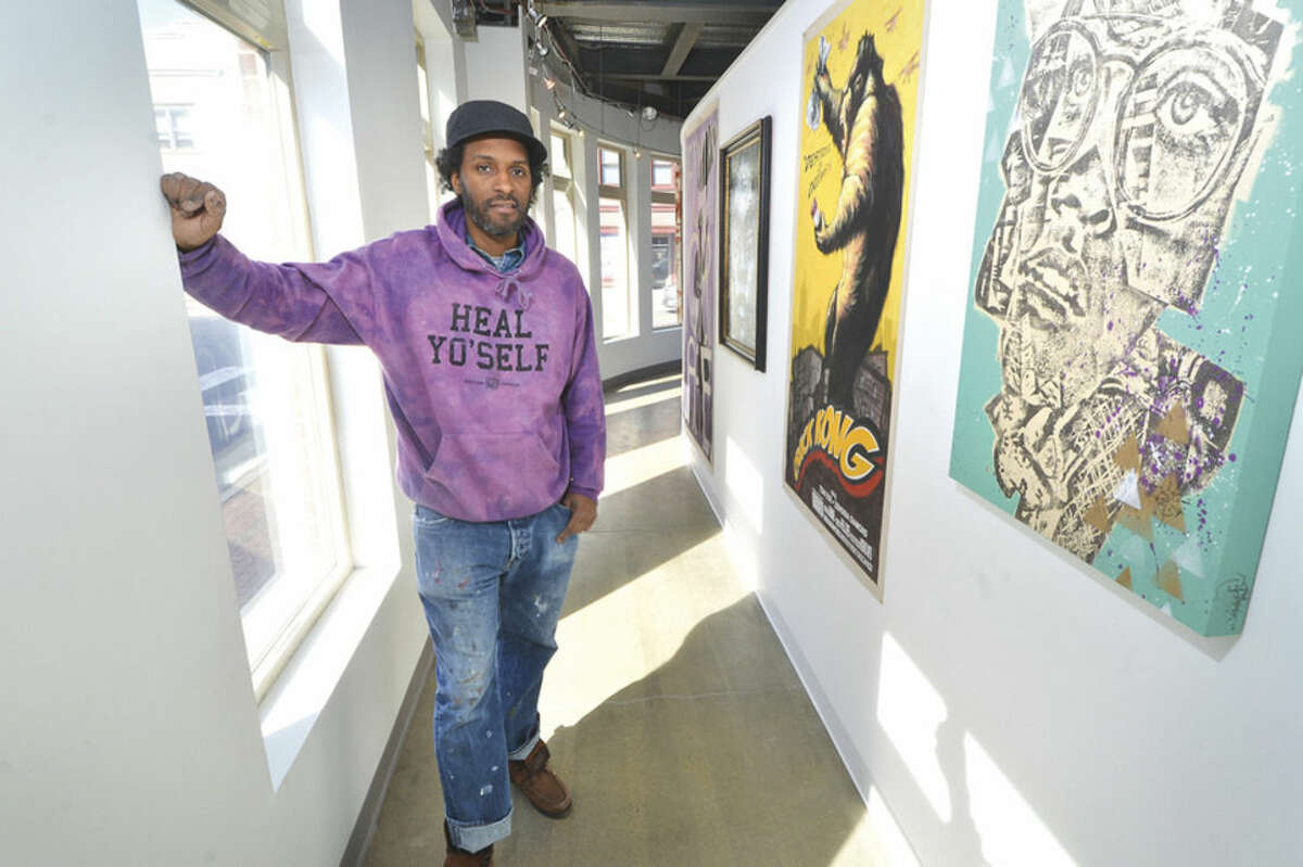 Hour Photo/Alex von Kleydorff Artist Jahmane near two of his works, 'Crack Kong', Acrylic on Canvas and 'Genome 42' hand painted wood panel at SoNo's Sidewalk Gallery.