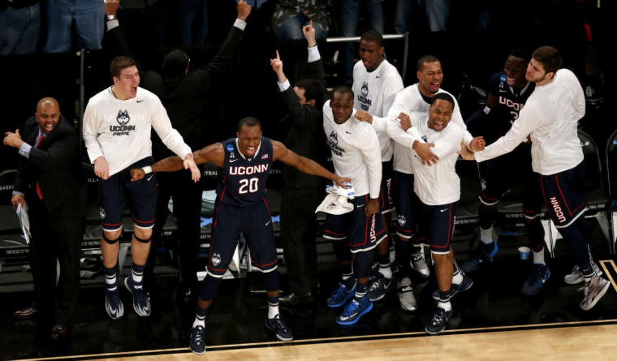 Connecticut players react during the second half in a regional semifinal at the NCAA college basketball tournament against Michigan State, Sunday, March 30, 2014, in New York. (AP Photo/Julio Cortez)