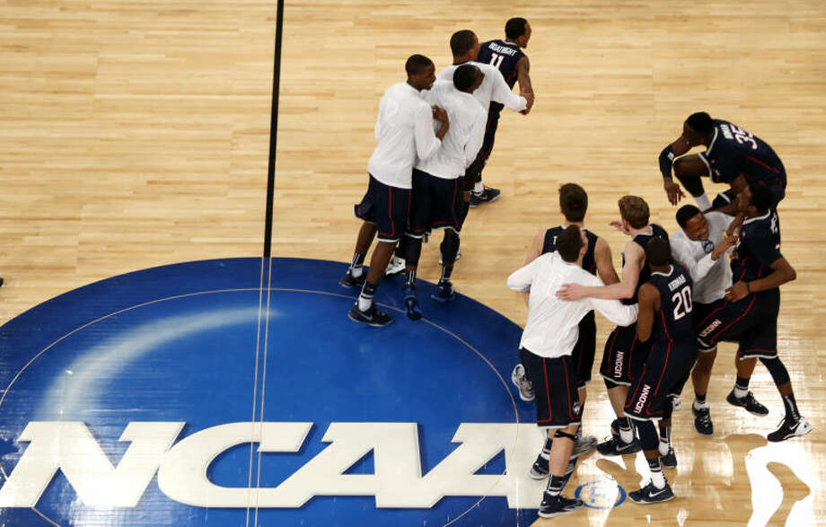 Connecticut players celebrate after defeating Michigan State during a regional final at the NCAA college basketball tournament on Sunday, March 30, 2014, in New York. (AP Photo/Julio Cortez)