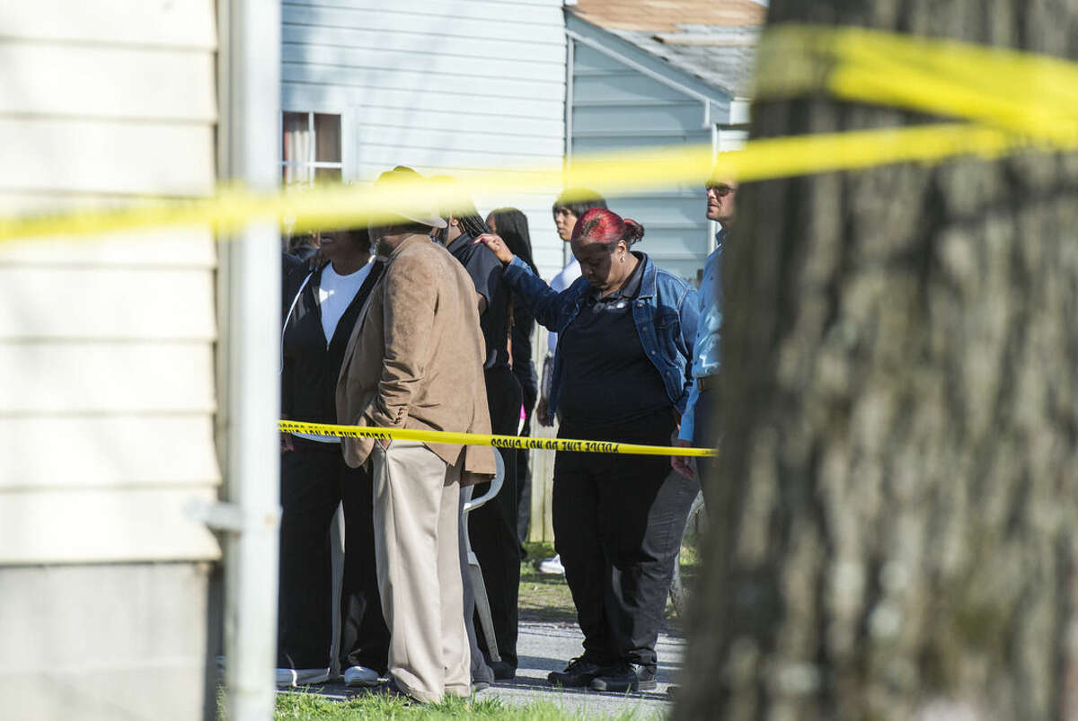 Onlookers gather outside of a house, where police say seven children and one adult have been found dead Monday, April 6, 2015, in Princess Anne, Md. Police were sent to the home Monday after being contacted by a concerned co-worker of the adult. (AP Photo/The Daily Times, Joe Lamberti)