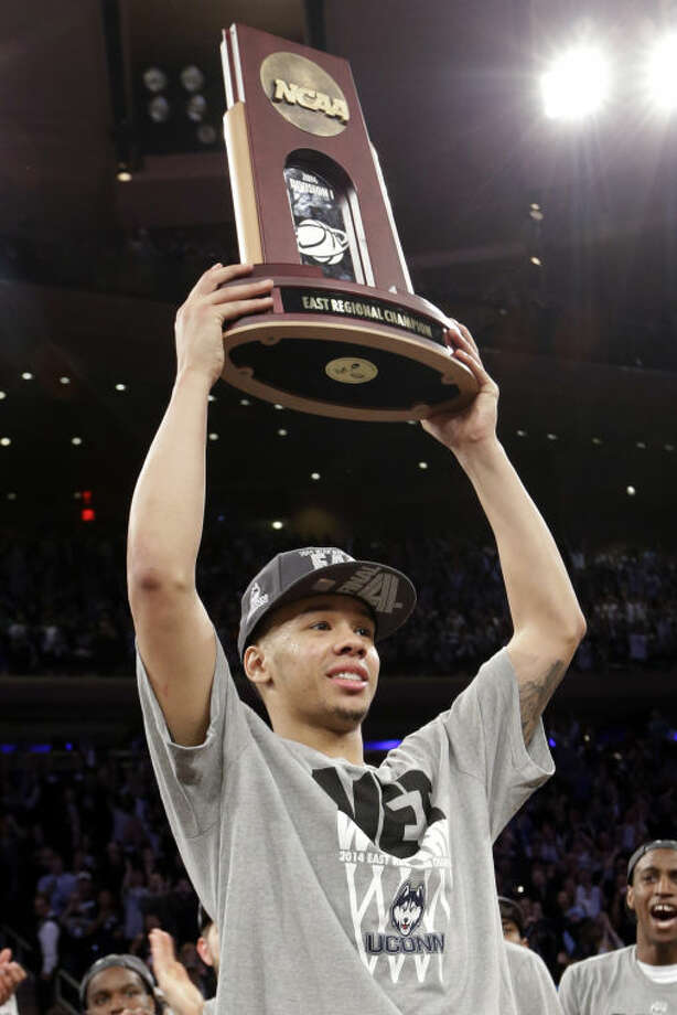 Connecticut guard Shabazz Napier holds up the east regional trophy after his team beat Michigan State 60-54 during a regional final at the NCAA college basketball tournament, Sunday, March 30, 2014, in New York. (AP Photo/Frank Franklin II)