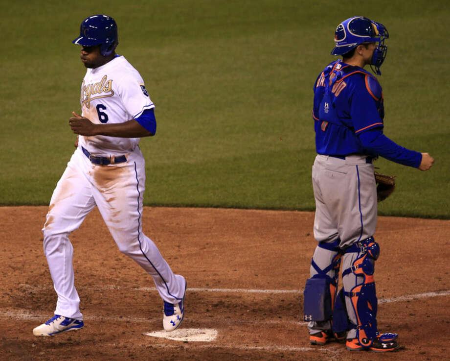 Kansas City Royals' Lorenzo Cain (6) scores a run past New York Mets catcher Travis d'Arnaud (7) during the fourth inning of a baseball game at Kauffman Stadium in Kansas City, Mo., Sunday, April 3, 2016. (AP Photo/Orlin Wagner)