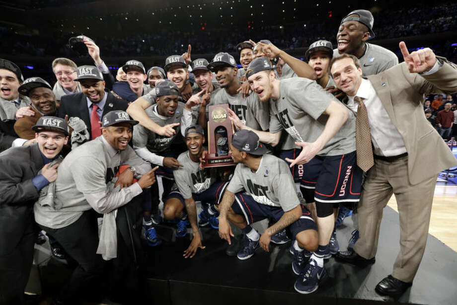 The Connecticut team poses for photographs after a regional final against Michigan State in the NCAA college basketball tournament ,Sunday, March 30, 2014, in New York. Connecticut won 60-54. (AP Photo/Frank Franklin II)