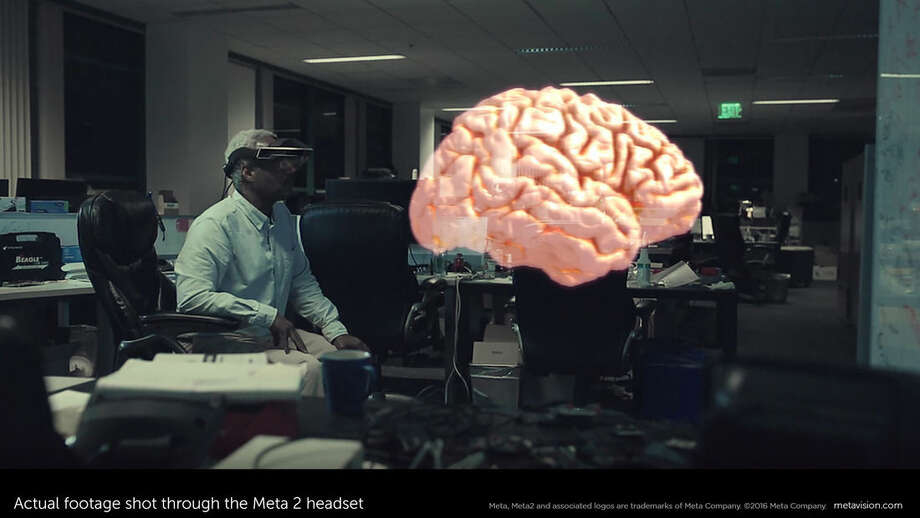 This February 2016 image provided by Meta shows actual footage of a model of a brain shot through the Meta 2 headset, while Meta employee Forest Rouse wears a Meta 2 headset, background left, in Redwood City, Calif. While startups like Meta, Magic Leap and Atheer have been making the most visible progress in augmented reality so far, technology heavyweights are also eyeing it. (Meta via AP) MANDATORY CREDIT