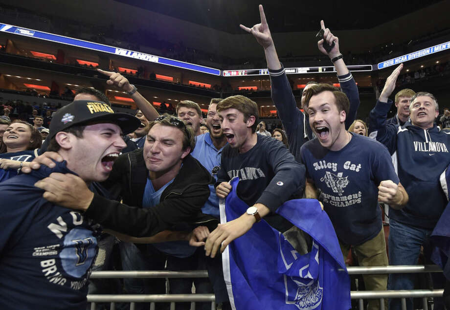 Villanova guard Ryan Arcidiacono, left, is embraced by fans after a regional final men's college basketball game in the NCAA Tournament against Kansas, Saturday, March 26, 2016, in Louisville, Ky. Villanova won 64-59.(AP Photo/John Flavell)