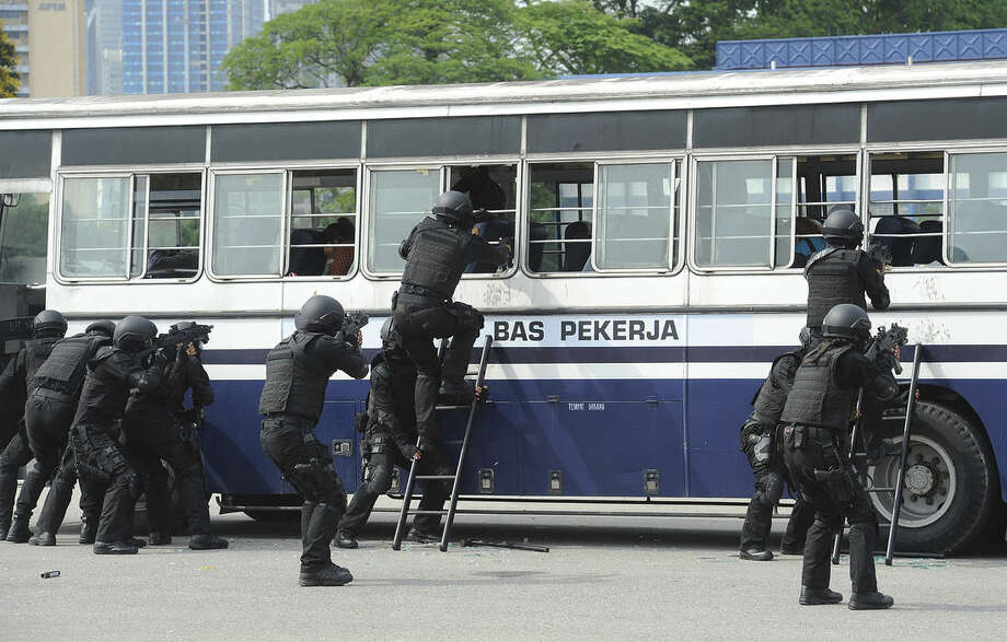 In this Wednesday, March 25, 2015 photo, Malaysia Police special force unit tries to break into a bus during an exercise against a terrorist attack at a police training camp in Kuala Lumpur, Malaysia. Malaysia revived detention without trial when lawmakers approved an anti-terror law Tuesday, April 7, 2015 that the government said was needed to fight Islamic militants, but critics assailed as a giant step backward for human rights in the country. (AP Photo) MALAYSIA OUT, NO SALES, NO ARCHIVE