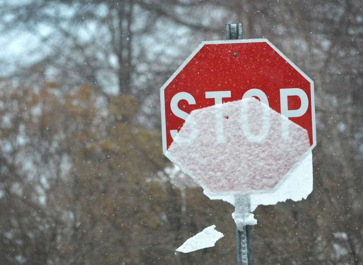 Hour Photo/Alex von Kleydorff A coating of snow in the shape of a the stop signs slides down the front and is blown away in the wind during Mondays winter weather