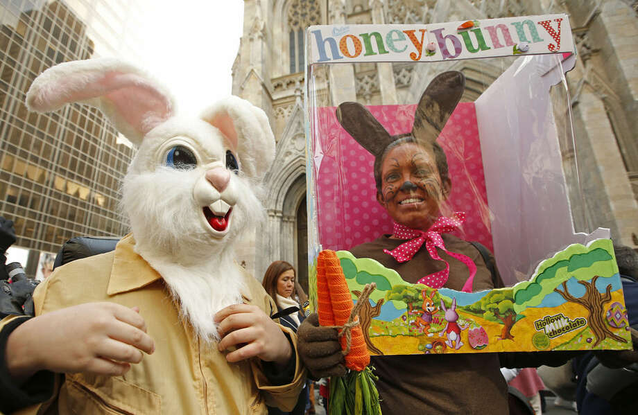 Maxwell Kalba and Judth Stuck, of West Hempstead, N.Y., pose for photographers during the annual Easter parade along Fifth Avenue in front of St. Patrick's Cathedral, Sunday, March 27, 2016, in New York. Stuck admitted Maxwell, 12, was tiring of wearing his rabbit head costume because it was so heavy. (AP Photo/Kathy Willens)