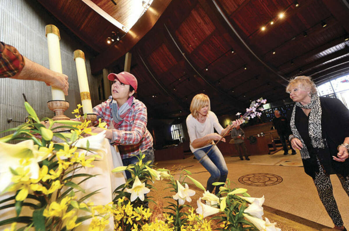 Hour photo / Erik Trautmann Members of the St. Philip Artist Guild, including co-chair Dollka Morico, Melissa Chieffalo and Gayle Geckler, decorate the St. Philip Church for Easter.