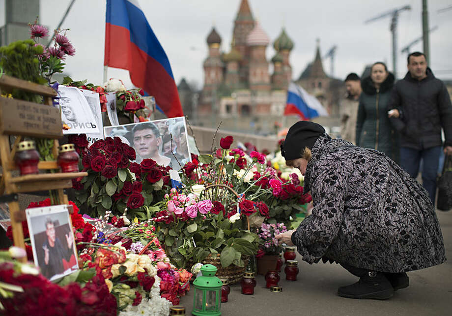 A woman lights votive candles at a place where Boris Nemtsov, a charismatic Russian opposition leader and sharp critic of President Vladimir Putin, was gunned down on Feb. 27, 2015 near the Kremlin in Moscow, Russia, Tuesday, April 7, 2015. Supporters of Russian opposition politician Boris Nemtsov gathered at a Moscow bridge where he was gunned down Feb. 27 to commemorate 40 days since his death, a special day in the Orthodox Christian tradition. (AP Photo/Alexander Zemlianichenko)